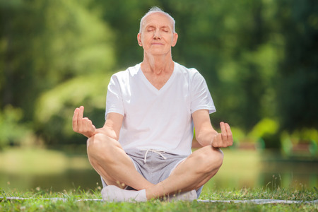 meditating: Peaceful senior man meditating seated on a blanket in a park by a lake Stock Photo