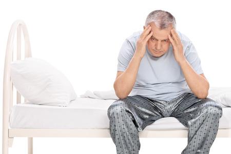 Gefrustreerd senior zittend op een bed in zijn pyjama en op zoek naar beneden op een witte achtergrond