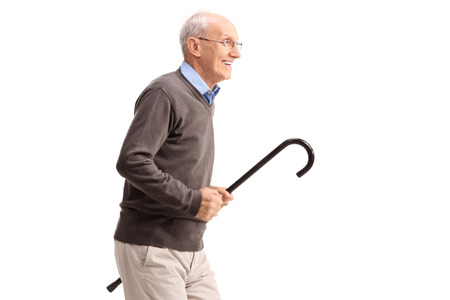 healthy aging: Joyful senior gentleman carrying a cane in his hand and running isolated on white background Stock Photo