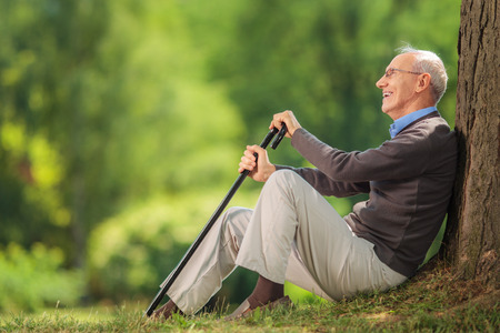 carefree: Senior gentleman holding a cane seated by a tree in a park on a beautiful summer day