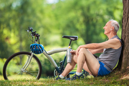 Ciclista mayor que se sienta por un árbol en un parque con una botella de agua en la mano y escuchar música en los auriculares Foto de archivo