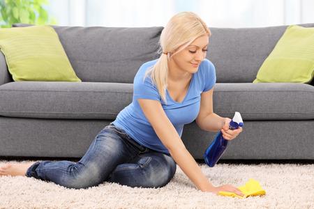 mujer limpiando: Joven mujer rubia limpiar una alfombra delante de un sof� de color gris con un trapo en el pa�s