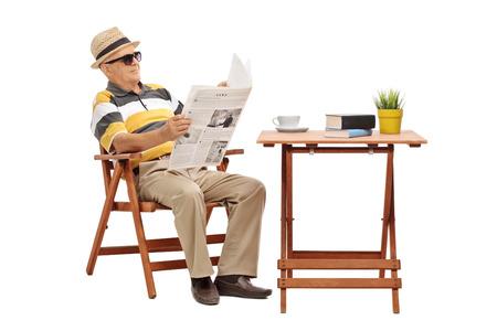 silla de madera: Señor mayor que se sienta en una mesa de café y leyendo un periódico aislado en fondo blanco