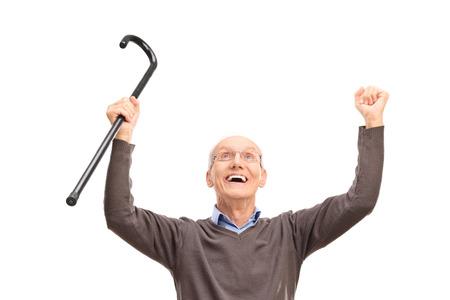 Überglücklich Senior hält einen schwarzen Stock ein Nachschlagen isoliert auf weißem Hintergrund
