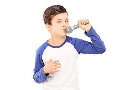 cantando: Alegre poco canto niño en un micrófono aislado en el fondo blanco