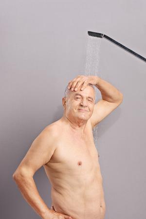 desnudo masculino: Tiro vertical de una persona mayor alegre que toma una ducha y mirando a la cámara