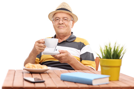 1 mature man: Senior gentleman drinking coffee seated at a wooden table with a few croissants on a plate in front of him isolated on white background