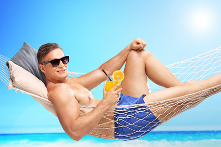 beach hunk: Handsome young man holding an orange cocktail and lying in a hammock at a sunny beach by an ocean Stock Photo