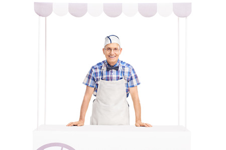 ice cream stand: Senior ice cream seller with a white cap and apron standing behind an ice cream stand and looking at the camera isolated on white background Stock Photo