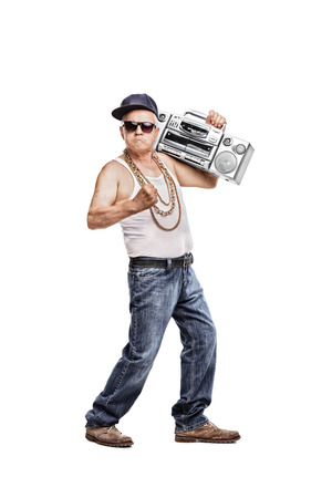 cocky: Full length portrait of a mature man in hip-hop outfit holding a ghetto blaster and looking at the camera isolated on white background