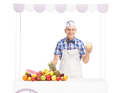 jerk: Senior soda jerk holding a glass of lemonade and standing behind a stall with a bunch of fruits on it isolated on white background Stock Photo