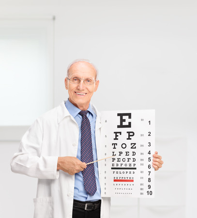eye chart: Mature optician holding an eye chart and pointing on it with a wooden stick in a hospital Stock Photo