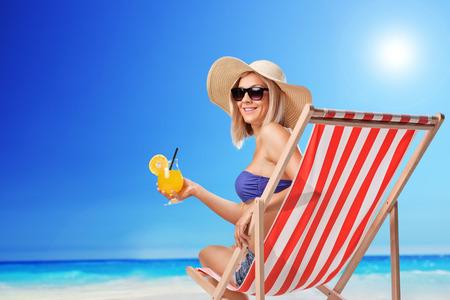 Junge Frau sitzt auf einer Sonnenliege mit einem orange-Cocktail in der Hand und schaut in die Kamera auf einem sonnigen Strand Standard-Bild - 43647569