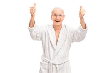 overjoyed: Studio shot of an overjoyed senior in a white bathrobe giving two thumbs up and looking at the camera isolated on white background Stock Photo