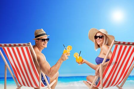 Junger Mann und Frau sitzen auf Liegestühlen und halten Cocktails an einem sonnigen Strand