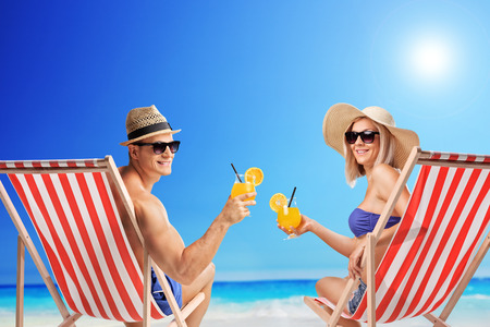 drink at the beach: Young man and woman sitting on sun loungers and holding cocktails at a sunny beach