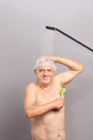 scrubbing: Vertical shot of a senior with a shower cap taking a shower and scrubbing himself with a bath brush