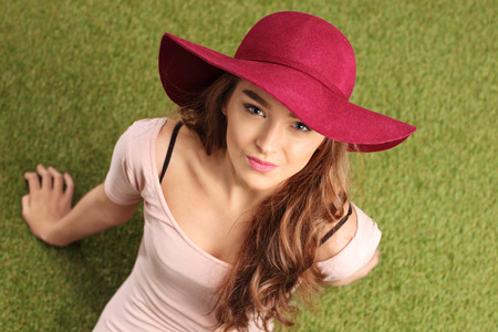 chic woman: High angle shot of a cheerful young woman with a stylish hat sitting on grass and looking at the camera Stock Photo