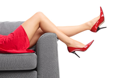 白い背景に分離されたグレーのソファに横たわっている赤いハイヒールで女性の脚の上のクローズ アップ