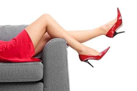 빨간색 하이힐에 흰색 배경에 고립 된 회색 소파에 누워있는 여성의 다리에 근접