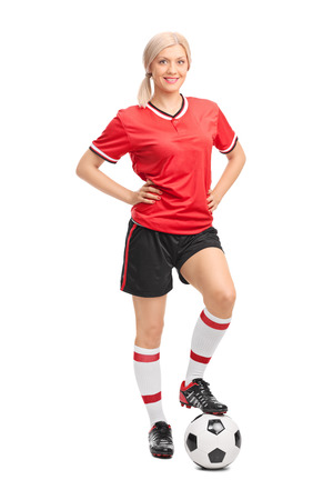 female soccer: Full length portrait of a female soccer player in red jersey posing with a soccer ball under her foot isolated on white background