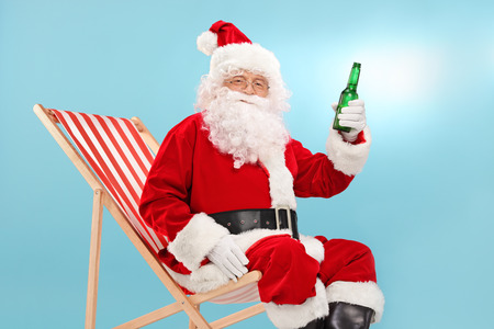christmas hat: Santa Claus holding a bottle of beer seated on a sun lounger and looking at the camera with blue sky in the background