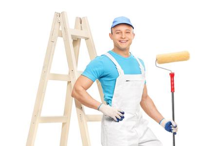 pintor: Pintor de casas de sexo masculino en un limpio guardapolvos blancos, sosteniendo un rodillo de pintura y apoyado en una escalera aislados en fondo blanco