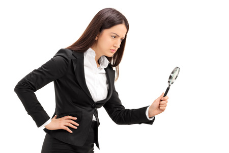 controlling: Businesswoman looking through a magnifying glass isolated on white background Stock Photo