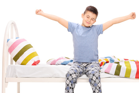 bedroom bed: Cute little boy in pajamas stretching himself seated on a bed isolated on white Stock Photo