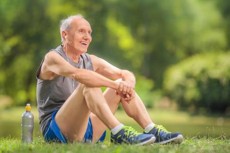 Athletic senior in sportkleding zittend op het gras in een park en het luisteren naar muziek op de koptelefoon Stockfoto