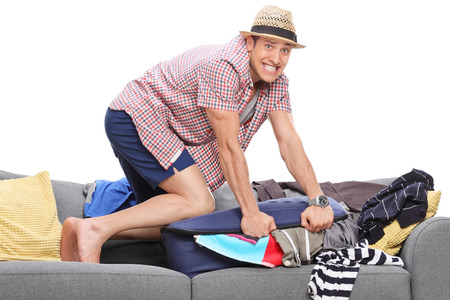 lot of: Young man packing a lot of clothes into one suitcase and looking at the camera isolated on white