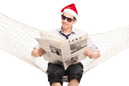 personas leyendo: Individuo joven con sombrero de Santa sentado en una hamaca y leyendo un peri�dico aislado en blanco Foto de archivo
