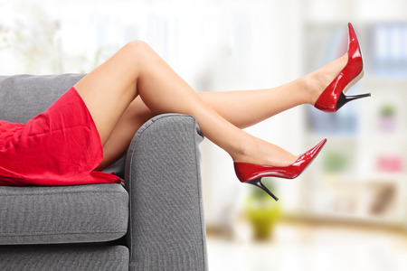 fcef4fb43c4 Close-up on female legs in red high heels lying on a gray couch indoors