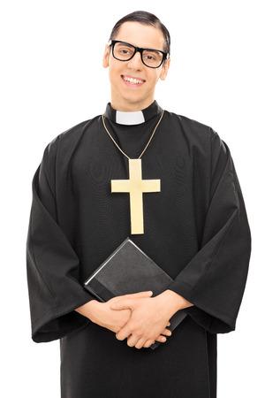 religion catolica: Tiro vertical de un joven sacerdote católico celebración de la Biblia y mirando a la cámara aislada en el fondo blanco
