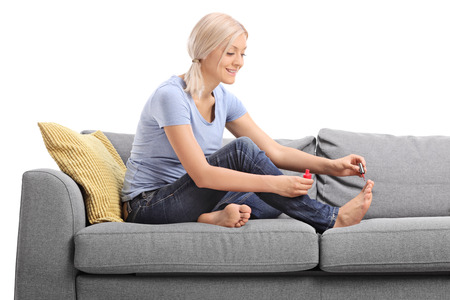 Young blond woman polishing her toenails with a red nail polish seated on a gray sofa isolated on white background Stock Photo