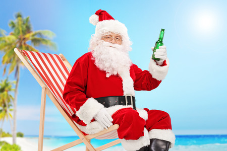 relaxing beach: Santa Claus holding a bottle of beer and looking at the camera seated on a beach on a sunny day