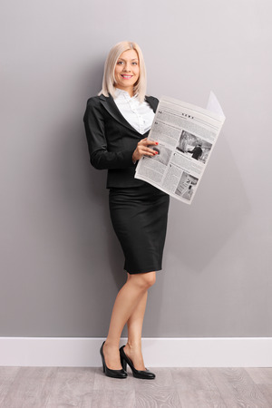 formal wear clothing: Full length portrait of a young blond businesswoman holding a newspaper and looking at the camera
