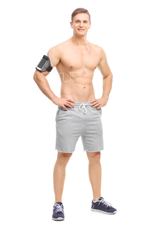 Retrato de cuerpo entero de un atleta joven descamisado escuchar música en su teléfono celular y mirando a la cámara aislada en el fondo blanco Foto de archivo