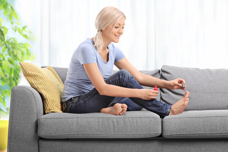 toenails: Young woman polishing her toenails and smiling seated on a gray couch at home