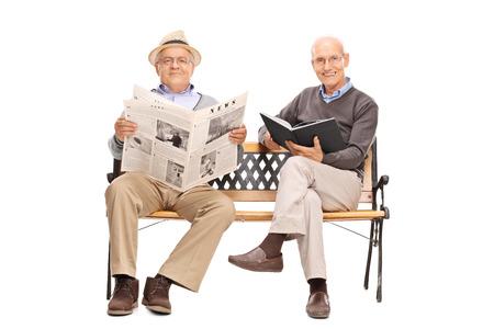 oude krant: Twee senior heren zittend op een bankje en houden van een boek en een krant op een witte achtergrond