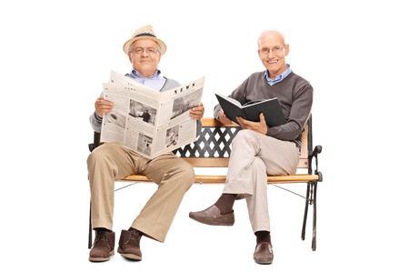 sitting on a bench: Two senior gentlemen sitting on a bench and holding a book and a newspaper isolated on white background