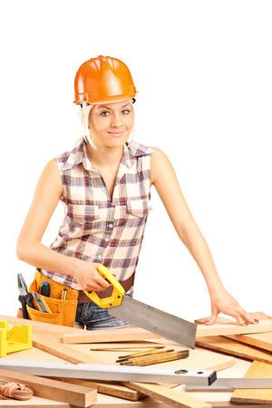 serrucho: Tiro vertical de un carpintero mujer con un casco naranja cortar un tablón de madera con una sierra de mano aisladas sobre fondo blanco