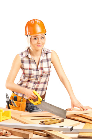 woodworker: Vertical shot of a female carpenter with an orange helmet cutting a wooden plank with a handsaw isolated on white background