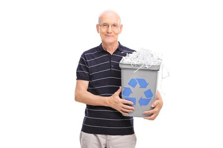 papelera de reciclaje: Caballero mayor que sostiene una papelera de reciclaje llena de papel picado y mirando a la c�mara aislada en el fondo blanco