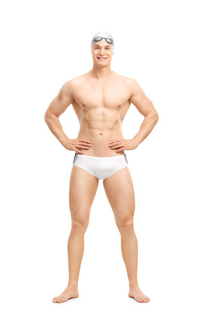 Full length portrait of a young handsome swimmer posing in white swim trunks isolated on white background