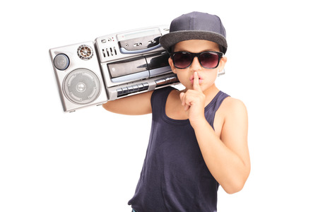 shush: Little boy in hip-hop outfit carrying a ghetto blaster and holding finger on his lips isolated on white background