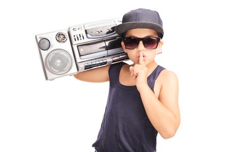 equipo de sonido: Niño pequeño en equipo del hip-hop que lleva un ghetto blaster y manteniendo el dedo en los labios aislados en fondo blanco Foto de archivo