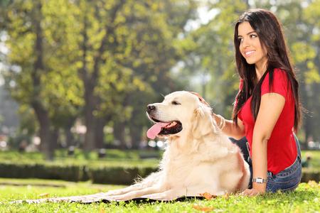 mujer sola: Bella joven sentado en la hierba con su perro en un parque Foto de archivo