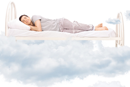Young man sleeping on a comfortable bed in clouds isolated on white Stock Photo