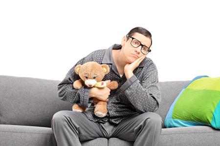homme triste: Homme triste en pyjama tenant un ours en peluche assis sur un canapé isolé sur blanc Banque d'images